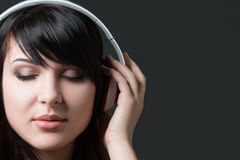 Close-up portrait of young woman listening to music Stock Image