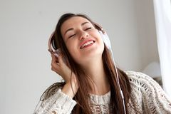 Close up young woman listening to music with eyes closed. Close up portrait of young woman listening to music with eyes closed Royalty Free Stock Images