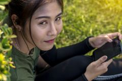 Close-up portrait of young woman with mobile in garden. stock photography