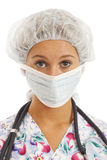 Close-up portrait of young woman nurse. In scrubs with mask and cap Stock Photography