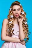 Fashion photo of young woman against blue background wearing pink dress and hair pins look like butterflies. Close-up portrait of young woman posing against blue royalty free stock photo