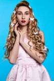 Fashion photo of young woman against blue background wearing pink dress and hair pins look like butterflies. Close-up portrait of young woman posing against blue stock images