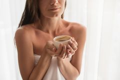 Close-up portrait of young woman relaxing at cozy atmosphere nex. T to window. Caucasian woman wearing white towel with cup of hot chocolate or coffee in her Royalty Free Stock Images