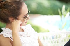 Young woman deep in thought. Close-up portrait of young woman sitting outdoor and looking deep in thought stock photo