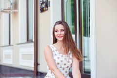 Close up portrait of a young woman smiling and looking to side sitting on steps royalty free stock photos