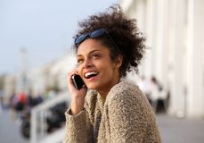 Close up portrait of a young woman smiling with mobile phone Royalty Free Stock Images