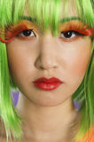 Close-up portrait of young woman wearing green wig and orange eyelashes over gray background Royalty Free Stock Image