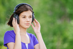 Close-up portrait of young woman wearing headphones. Close-up portrait of young beautiful brunette woman wearing headphones and propping up her face at summer Stock Image