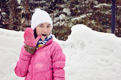 Close-up portrait of young woman in white winter hat and pink jacket at the rink, smiling widely and waving at the camera. Hello c stock image