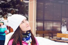Close-up portrait of young woman in white winter hat at the rink, stands and dreams of looking into the sky.  Royalty Free Stock Photography