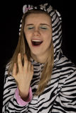 Close up portrait of a young woman yawning in cat pajamas Stock Images