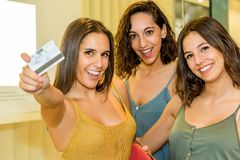 Young woman holding credit card next to girlfriend shoppers. stock images