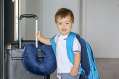Close-up portrat of cute smiling little baby boy with big backpack and suitcase with travelling pillow stay near open door ready t. O leave, prepared for travel royalty free stock photos