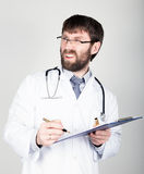 Close-up portret of a Doctor holding a map-case for note, stethoscope around his neck. he discontentedly looking at the Royalty Free Stock Image