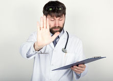 Close-up portret of a Doctor holding a map-case for note, stethoscope around his neck. He held up his hand, palm forward royalty free stock image