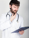 Close-up portret of a Doctor holding a map-case for note, stethoscope around his neck. He rubs his chin. different Stock Images