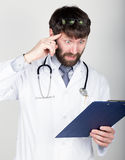 Close-up portret of a Doctor holding a map-case for note, stethoscope around his neck. He twists his index finger at his Royalty Free Stock Image