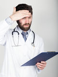Close-up portret of a Doctor holding a map-case for note, stethoscope around his neck. He wipes his forehead. different Stock Photography