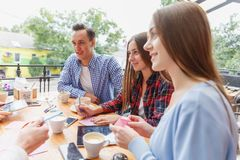 Modern happy students working at the cafe together on a blurred background. Active lifestyle concept. royalty free stock images