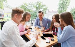 Modern happy students working at the cafe together on a blurred background. Active lifestyle concept. Royalty Free Stock Image
