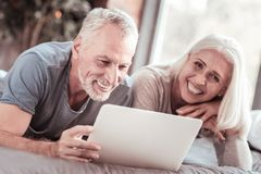 Close up of positive elderly family with a laptop royalty free stock photo