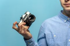 Close-up - positive young male photographer holding vintage camera. Against a blue background royalty free stock image