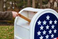 Close-up Of Postman Putting Letters Mailbox American flag. Close-up Of Postman Putting Letters In Mailbox American flag Stock Photos