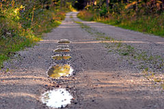 Pot holes in dirt road Stock Photography