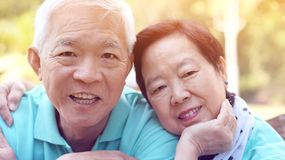 Close up potrait of smiling Asian senior couple on bright green Stock Image