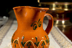 Close-up of pottery jug to serve wine or water on an embroidered table mat Stock Photography