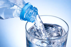 Close-up Pouring glass of water from plastic bottle on blue background Stock Images