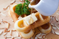 Close-up pouring honey from top of waffles and nut. Which has parsley and cheese on top of waffles on wood plate for breakfast Stock Photography