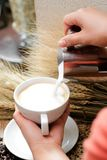 Close up pouring milk into coffee making hot latte - Soft focus Stock Image