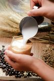 Close up pouring milk into coffee making hot latte - Soft focus Stock Images