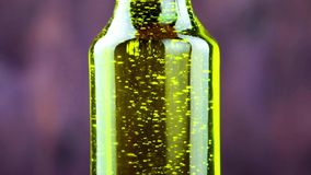 Close-up of pouring olive oil in the bottle on wood background