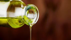 Close-up of pouring olive oil with the bottle on wood background stock video footage
