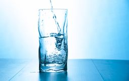 Close up pouring purified fresh drink water from the bottle in glass. With copy space Stock Photos