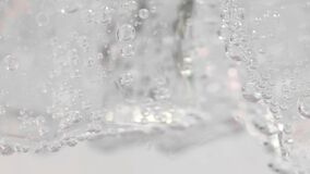 Close-up pouring soda into the glass with ice. Food background. Cold beverage. 4K UHD video 3840x2160