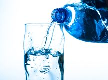 Pouring water from bottle into glass on blue background Stock Photography