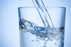 Close-up pouring water into glass on blue background Stock Image