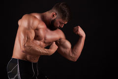 Close-up of a power fitness man`s hand. Strong handsome young bodybuilder demonstrate his muscles and biceps Royalty Free Stock Photo