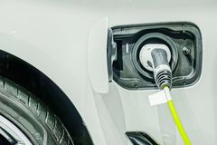 Close up of the power supply plugged into an electric car being charged. A Close up of the power supply plugged into an electric car being charged stock photo