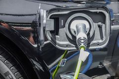 Close up of the power supply plugged into an electric car being charged. A Close up of the power supply plugged into an electric car being charged royalty free stock photography