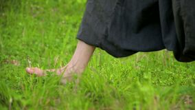 Close-up of a practicing man`s legs outdoors in the grass. Crossing bare feet in qigong exercises. The concept of a. Sports lifestyle in oriental culture 4k stock footage