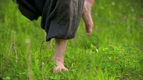 Close-up of a practicing man`s legs outdoors in the grass. Crossing bare feet in qigong exercises. The concept of a. Sports lifestyle in oriental culture 4k stock video footage
