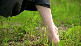Close-up of a practicing man's legs outdoors in the grass. Crossing bare feet in qigong exercises. The concept of a. Sports lifestyle in oriental culture 4k stock video footage