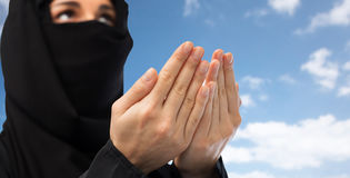 Close up of praying muslim woman in hijab over sky Stock Photo
