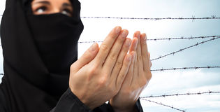 Close up of praying muslim woman over barb wire Royalty Free Stock Image