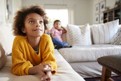 Close up of pre-teen girl lying on sofa watching TV in the living room, her younger brother sitting in the background, focus on fo. Reground stock image