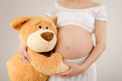 Close up on pregnant belly and a big teddy bear. Stock Image